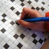 child's hand, writing in a crossword puzzle