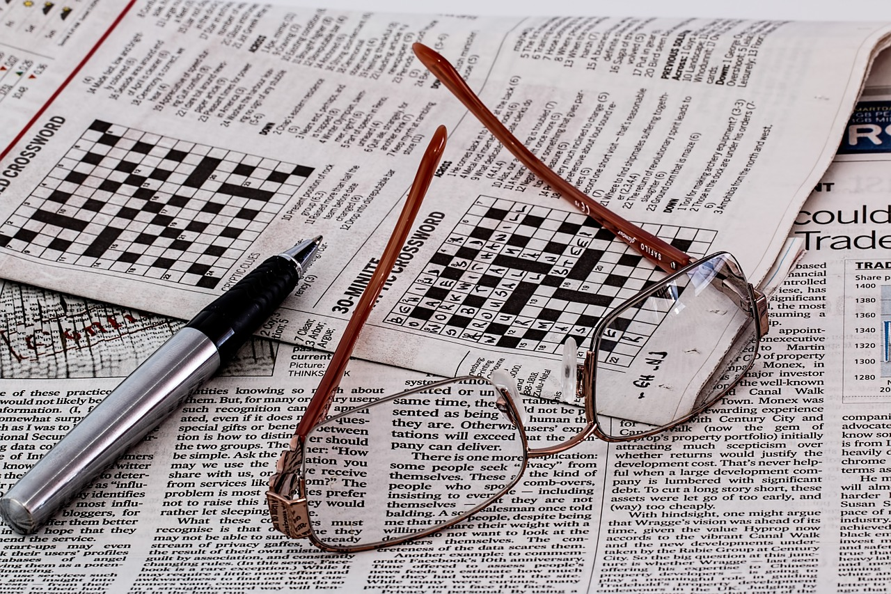 newspaper puzzle, glasses and pencil