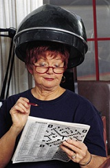 Lady sitting under hair dryer, solving a crossword