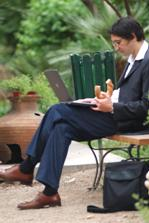 man sitting on park bench eating his lunch
